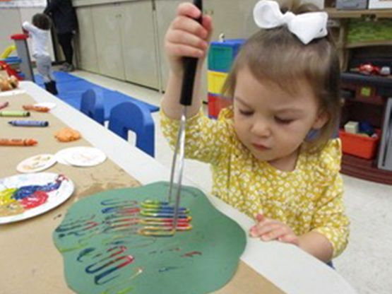 Little girl painting in Tiny Tots Program